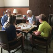 Seniors and children playing board game